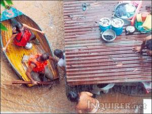 A family in San Mateo, Rizal flees their flooded home (Photo for the Philippine Daily Inquirer by Romy Homilla)