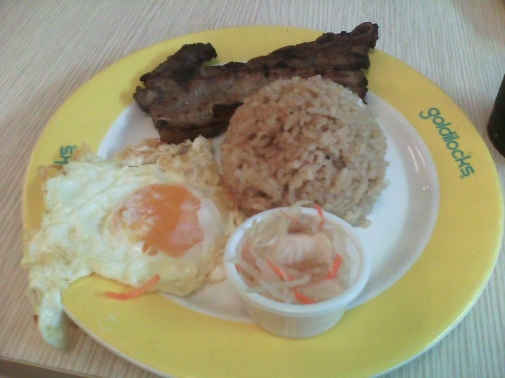 Grilled pork belly rib slice marinated adobo-style with soy-garlic rice, a fried egg, and papaya relish