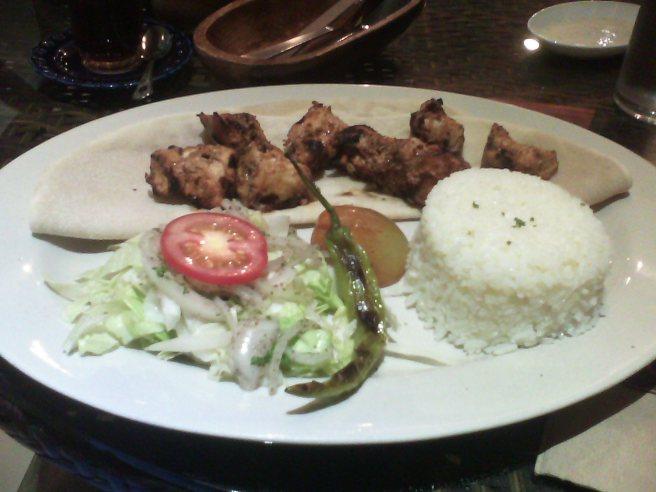 Chicken şiş kebab on lavash with rice and a salad